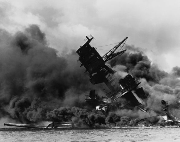 The USS Arizona during the attack. Photographer unknown. This photograph is in the public domain.