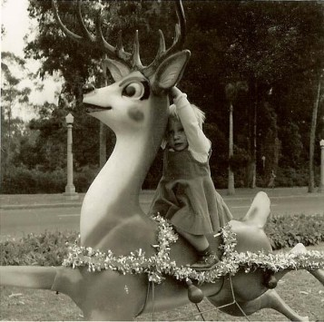 Little me sitting on one of Santa's reindeer, which is part of Balboa Park's annual holiday display
